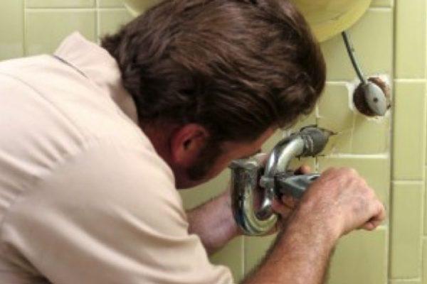 Plumber fixing drain pipe